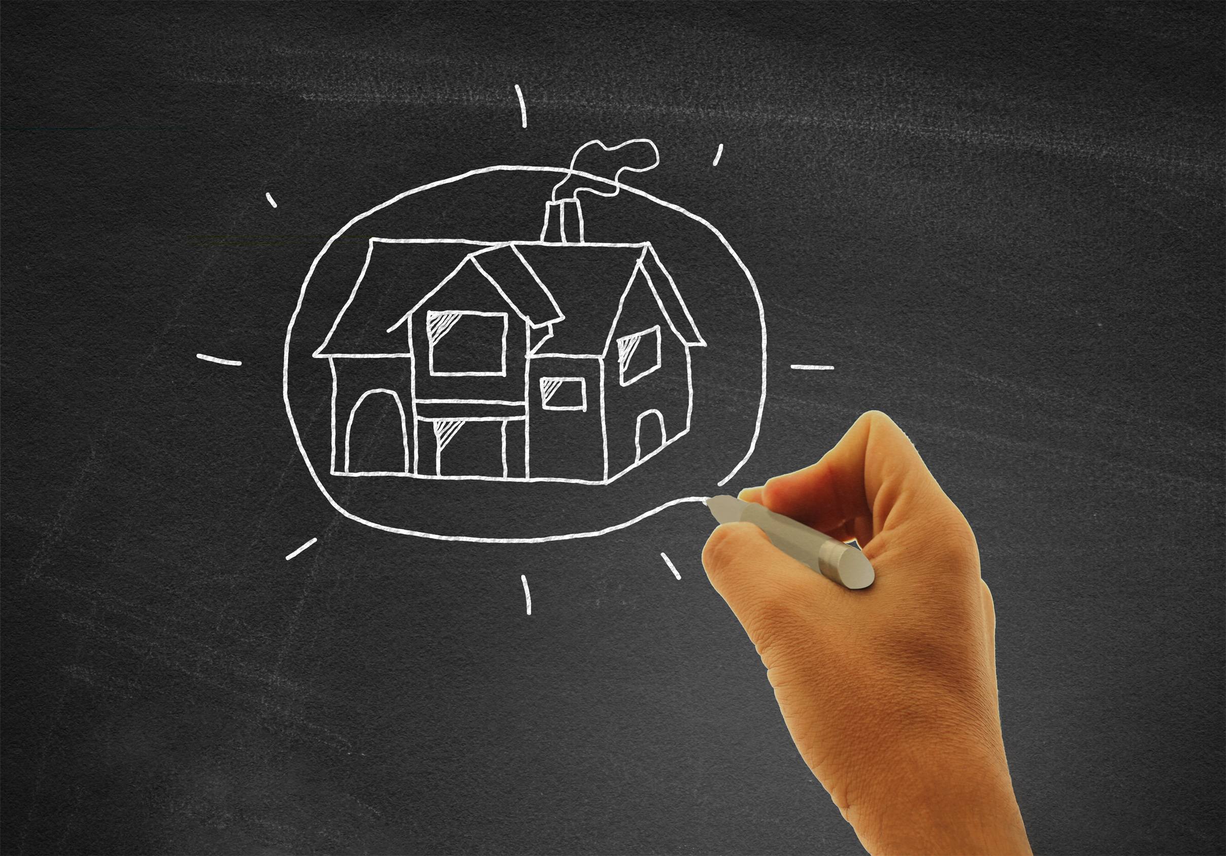 Hand drawing a house on blackboard — Real estate and housing con